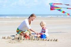 Mãe feliz e criança pequena que jogam na praia imagens de stock royalty free