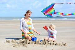 Mãe feliz e criança pequena que jogam na praia foto de stock royalty free