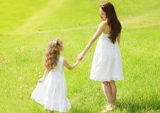 Mãe feliz e criança que guardam as mãos que andam no verão ensolarado Imagem de Stock Royalty Free