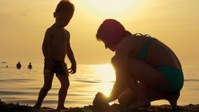 Mãe feliz e criança que jogam com a areia na praia contra o por do sol video estoque
