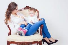 Mãe feliz e criança que sentam-se na casa da poltrona Foto de Stock