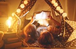 Mãe feliz e crianças da família que leem um livro na barraca no hom
