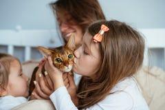 Mãe feliz e dois abraços de sorriso das filhas na cama foto de stock royalty free
