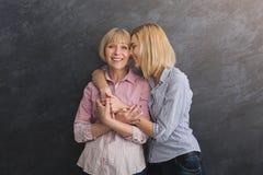 Mãe feliz e filha adultas que abraçam no fundo cinzento fotos de stock