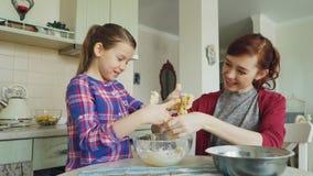 Mãe feliz e filha bonita que cozinham junto e que têm o divertimento Mamã que descola a massa pegajosa das mãos da menina e vídeos de arquivo