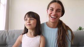 A mãe feliz e a filha bonito da criança fazem a chamada em linha distante
