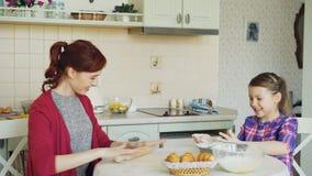 Mãe feliz e filha bonito que cozinham junto a fala na cozinha em casa no fim de semana Mãos de aplauso da menina filme