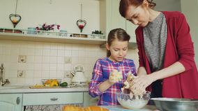 Mãe feliz e filha bonito que cozinham junto e que têm o divertimento que agita a massa nas mãos Família, alimento, casa e povos vídeos de arquivo