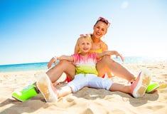 Mãe feliz e filha modernas que sentam-se no seacoast fotos de stock royalty free
