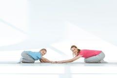 Mãe feliz e filha no sportswear que exercitam em esteiras da ioga fotografia de stock
