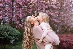 Mãe feliz e filha pequena com cabelo louro longo que abraçam no parque Conceito de família primavera, árvores de florescência foto de stock royalty free