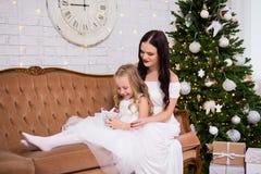 Mãe feliz e filha pequena que sentam-se na sala de visitas com Chr fotos de stock