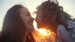 Mãe feliz e filha pequena sobre o por do sol, lento-movimento video estoque