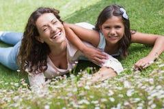 Mãe feliz e filha que encontram-se na grama Fotos de Stock