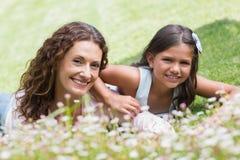Mãe feliz e filha que encontram-se na grama Imagens de Stock Royalty Free