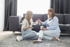 Mãe feliz e filha que falam ao comer o café na sala de visitas foto de stock