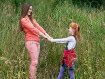 Mãe feliz e filha que guardam as mãos e que olham se Foto de Stock