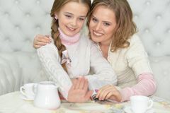 Mãe feliz e filha que olham as unhas ao ler o compartimento e ao beber o chá junto foto de stock