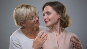 Mãe feliz e filha que olham in camera, relações fêmeas macias, conexão video estoque
