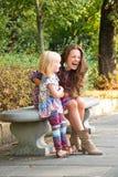 Mãe feliz e filha que têm o tempo do divertimento no parque Imagens de Stock Royalty Free