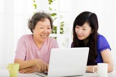 Mãe feliz e filha superiores que aprendem o portátil Imagem de Stock