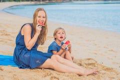 Mãe feliz e filho da família que comem uma melancia na praia As crianças comem o alimento saudável fotografia de stock