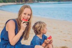 Mãe feliz e filho da família que comem uma melancia na praia As crianças comem o alimento saudável imagem de stock
