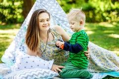 Mãe feliz e filho pequeno que jogam no parque bolhas O co fotografia de stock