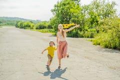 Mãe feliz e filho que jogam com o avião do brinquedo contra o fundo velho da pista de decolagem Viagem com conceito das crianças imagens de stock