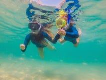 Mãe feliz e filho que mergulham no mar Olhe os peixes sob a água imagem de stock royalty free