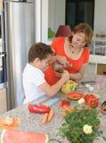 Mãe feliz e filho que preparam o almoço com um almofariz fotos de stock
