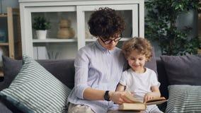 Mãe feliz e livro de leitura bonito da criança que olham imagens no sofá em casa