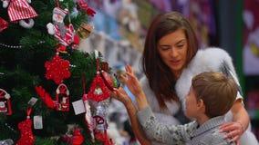 A mãe feliz e seu filho pequeno estão observando as decorações na árvore de Natal na alameda opinião lateral do close-up video estoque