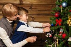 Mãe feliz e seu rapaz pequeno que decoram a árvore de Natal Imagem de Stock