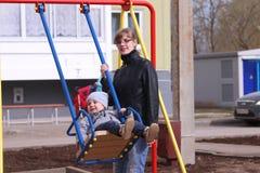 Mãe feliz e seus balanços pequenos do filho Fotografia de Stock