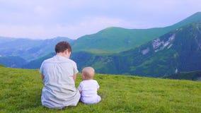 Mãe feliz e sua criança que olham dianteiras e que apontam ao céu Família no dia trekking nas montanhas fotografia de stock royalty free
