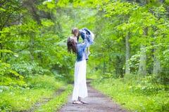 Mãe feliz e sua filha caucasiano pequena que levantam com expressão de beijo junto na floresta verde do verão Imagem de Stock Royalty Free