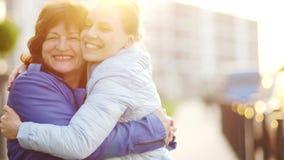 Mãe feliz e sua filha do aduit As mulheres abraçam delicadamente e olham alegremente a câmera Tradições da família matrizes vídeos de arquivo