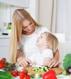 Mãe feliz e sua filha pequena na cozinha foto de stock