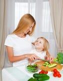 Mãe feliz e sua filha pequena na cozinha fotos de stock