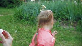 Mãe feliz e sua filha pequena que jogam junto bolhas de sabão exteriores, fundindo, tendo o divertimento no quintal nave filme