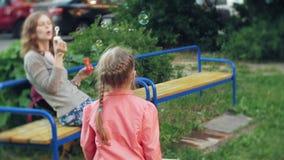 Mãe feliz e sua filha pequena que jogam junto bolhas de sabão exteriores, fundindo, tendo o divertimento no quintal nave video estoque