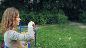 Mãe feliz e sua filha pequena que jogam junto bolhas de sabão exteriores, fundindo, tendo o divertimento no quintal nave vídeos de arquivo