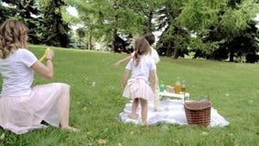Mãe feliz e suas duas crianças que jogam junto, bolhas de sabão de sopro e de travamento fora video estoque