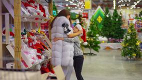 A mãe feliz está pondo o chapéu de Santa Claus sobre seu filho e está abraçando-o Despesa do tempo na alameda filme