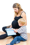 Mãe feliz grávida bonita com o isolador do livro de leitura do menino da criança Fotos de Stock Royalty Free