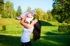 A mãe feliz joga o bebê no ar fotos de stock royalty free
