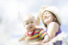 Mãe feliz no chapéu com seu filho pequeno no verão exterior Imagem de Stock