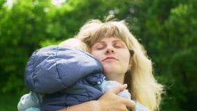 Mãe feliz nova loura com seu bebê no movimento lento da floresta filme