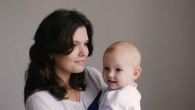 Mãe feliz nova que guarda sua criança recém-nascida Família em casa Mamã de sorriso bonita e bebê feliz junto